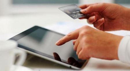 Человек оплачивает покупку через планшет